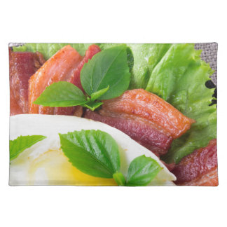Yolk, fried bacon, herbs and lettuce close-up placemat
