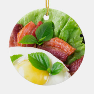 Yolk, fried bacon, herbs and lettuce close-up round ceramic ornament
