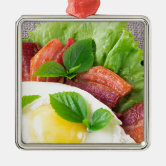 Yolk, fried bacon, herbs and lettuce close-up Silver-Colored square ornament