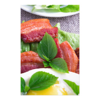 Yolk, fried bacon, herbs and lettuce close-up stationery