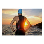 Young athlete triathlon in front of to sunrise poster