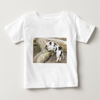 Young black and white piglet at tree trunk baby T-Shirt