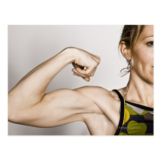 Young blond female flexes bicep muscle while postcard