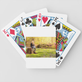 Young cool woman relaxing at spring time bicycle playing cards