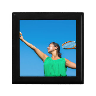 Young dutch woman with tennis racket and ball gift box