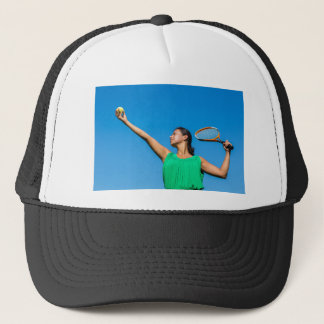 Young dutch woman with tennis racket and ball trucker hat