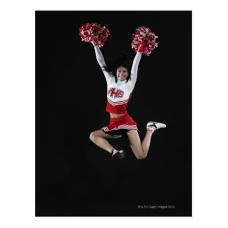 Young female cheerleader jumping in midair, arms postcard