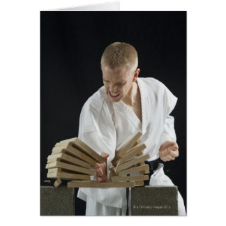Young man breaking boards with karate chop on card