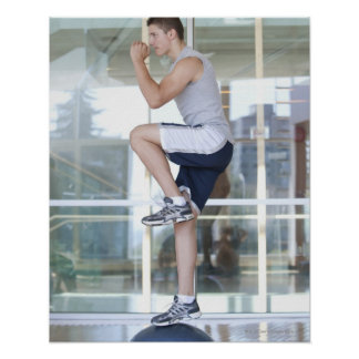 young man doing step-up exercises on a balance poster