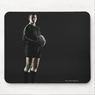 Young man holding rugby ball, portrait mouse pad