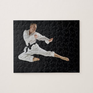 Young man performing karate kick on black puzzle