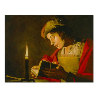 Young man reading by candlelight postcard