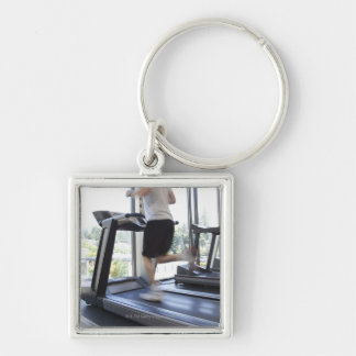 Young man running on a treadmill at health club, keychain