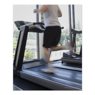 Young man running on a treadmill at health club, poster