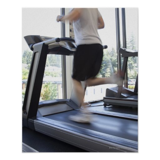 Young man running on a treadmill at health club, print