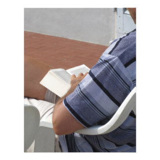 Young man sitting on chair reading book personalized letterhead