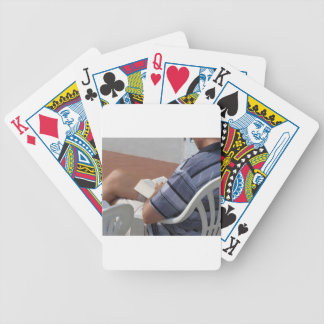 Young man sitting on chair reading book poker deck