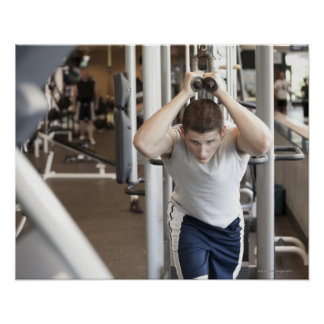 Young man working out his triceps on a cable poster