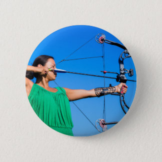 Young woman aiming arrow of compound bow 2 inch round button