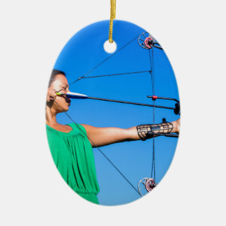 Young woman aiming arrow of compound bow ceramic ornament