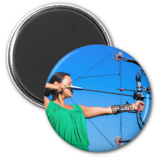 Young woman aiming arrow of compound bow magnet