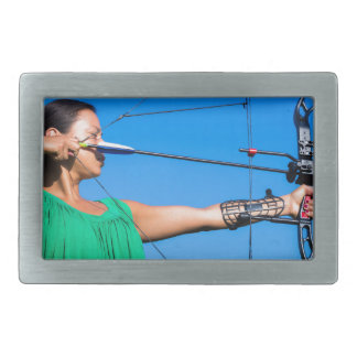 Young woman aiming arrow of compound bow rectangular belt buckle