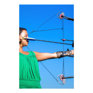 Young woman aiming arrow of compound bow stationery