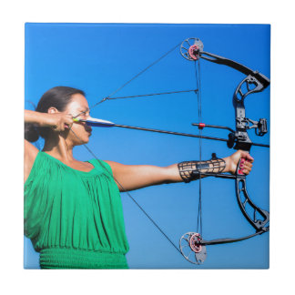 Young woman aiming arrow of compound bow tile