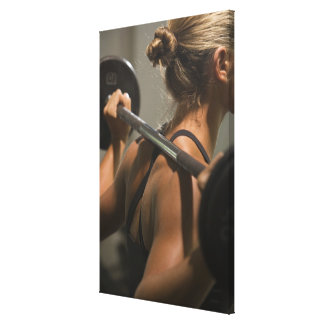 Young woman exercising with barbell, rear view canvas print