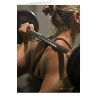 Young woman exercising with barbell, rear view card