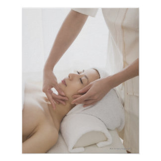 Young woman having facial massage poster