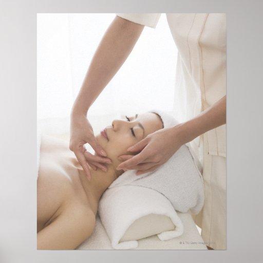 Young woman having facial massage poster