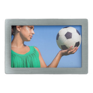 Young woman holding football on hand with blue sky belt buckles
