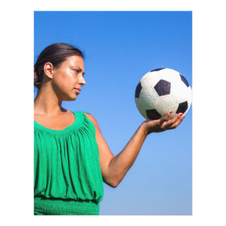 Young woman holding football on hand with blue sky letterhead