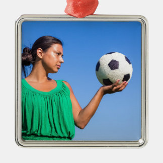 Young woman holding football on hand with blue sky metal ornament