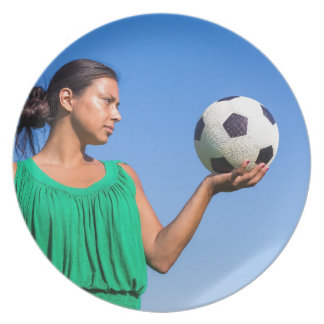 Young woman holding football on hand with blue sky party plates