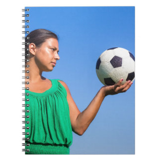 Young woman holding football on hand with blue sky spiral notebook