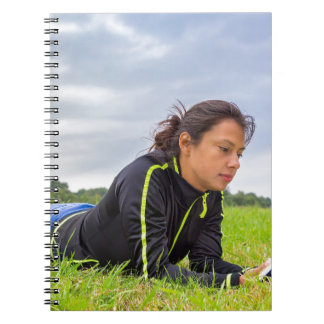 Young woman lying in grass reading book
