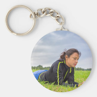 Young woman lying in grass reading book basic round button keychain