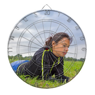 Young woman lying in grass reading book dartboard