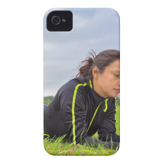 Young woman lying in grass reading book iPhone 4 case