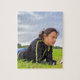 Young woman lying in grass reading book jigsaw puzzle