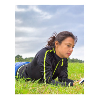 Young woman lying in grass reading book letterhead