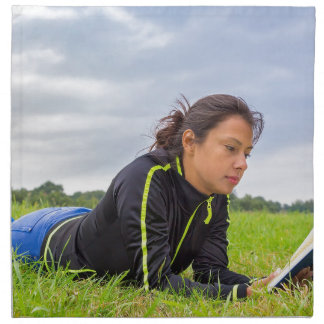 Young woman lying in grass reading book napkin