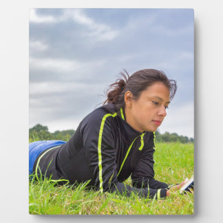 Young woman lying in grass reading book plaque
