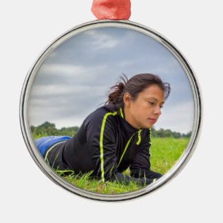 Young woman lying in grass reading book Silver-Colored round ornament