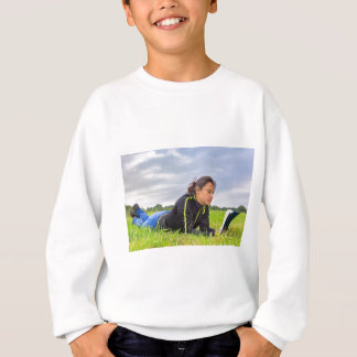 Young woman lying in grass reading book sweatshirt