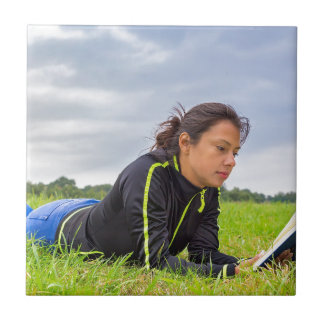 Young woman lying in grass reading book tile