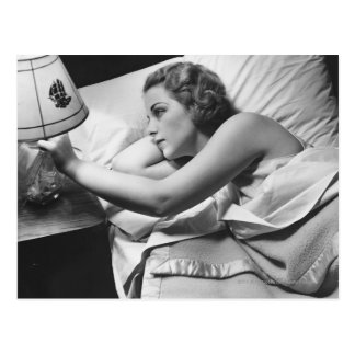 Young woman lying on bed turning off lamp on postcard