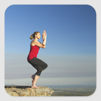 young woman practices yoga on a bluff in the square sticker